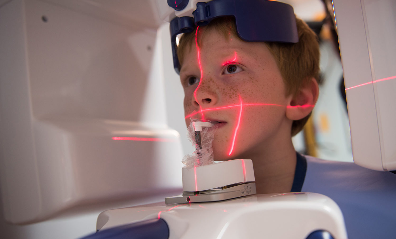 child being scanned by medical device